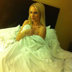 Nikki waiting for her man uncovered in bed under the sheets