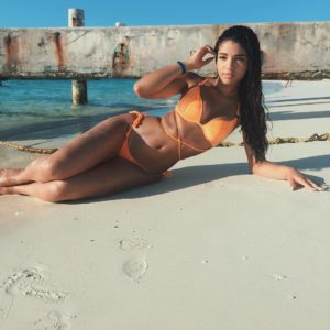 latina mama yoventura in orange bikini laying on her side