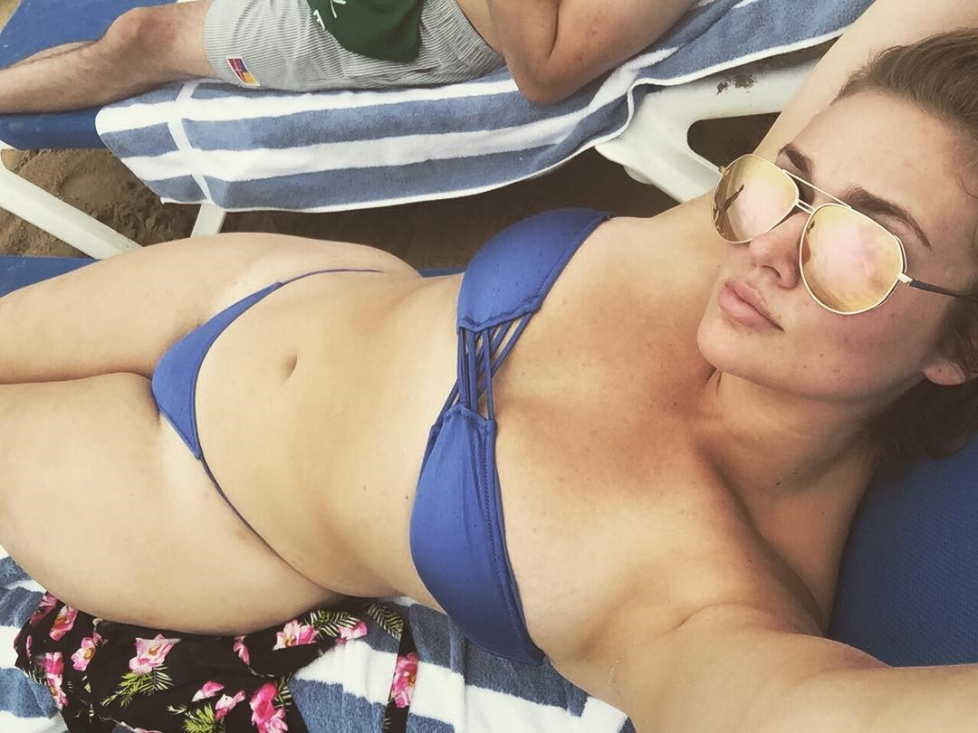 Hunter McGrady in purple swimsuit sitting next to pool