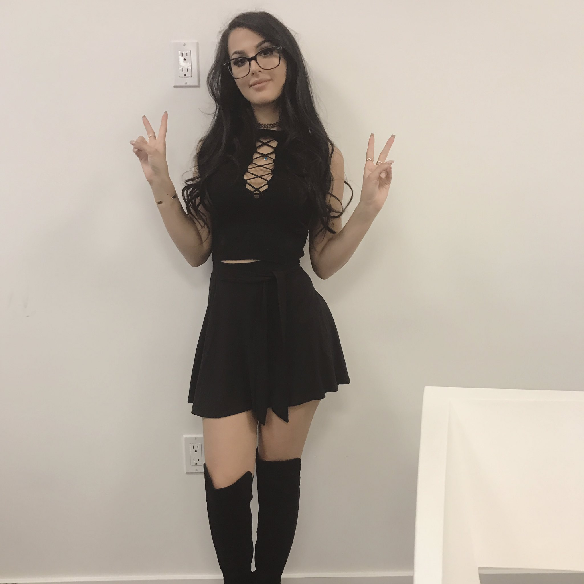 cosplay model sssniperwolf looking sexy in skirt and giving the peace sign