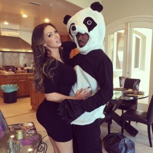 gorgeous nikki benz in tight black dress hugging a panda bear