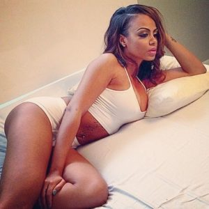 gorgeous model analicia chaves in tight shorts and white tank top laying on a bed